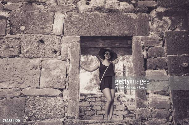 Full Length Portrait Of Young Woman Standing Amidst Wall