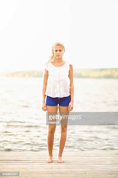 Full length portrait of young woman standing on boardwalk by lake