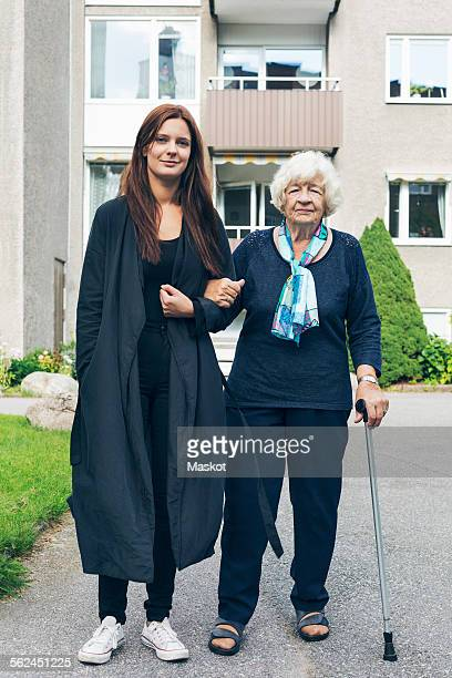 Full length portrait of young woman standing with grandmother outside house