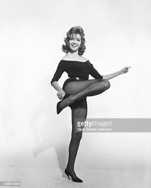 Full length portrait of Yvonne Monlaur French actress wearing a black longsleeve leotard and fishnet stockings holding a dance pose in a studio...