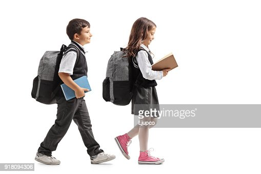 Full length profile shot a schoolboy and a schoolgirl with backpacks and books walking : Stock Photo
