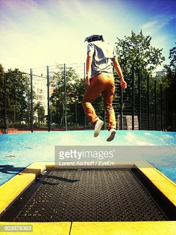 Full length rear view of a young man jumping on trampoline against trees