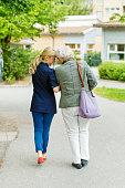 Full length rear view of affectionate female caretaker and senior woman walking on street