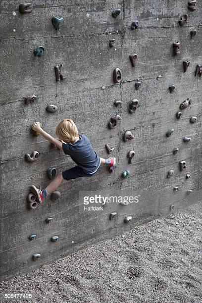 Full length rear view of boy climbing artificial rock