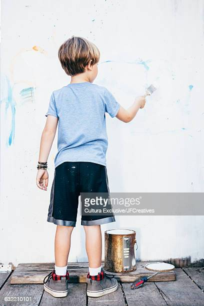 Full length rear view of boy in garden painting picture on wall