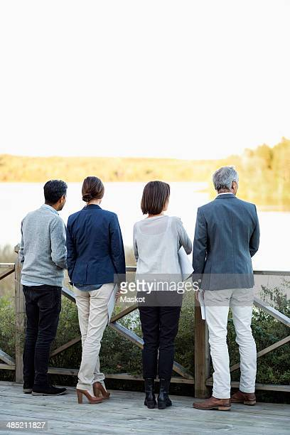Full length rear view of business people standing by railing on patio