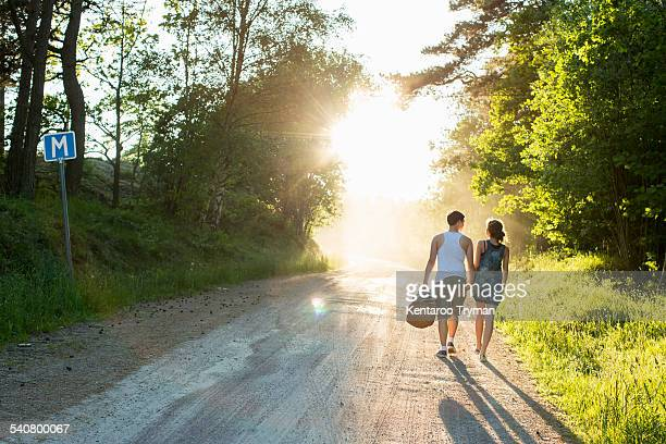 Full length rear view of couple walking on dirt road