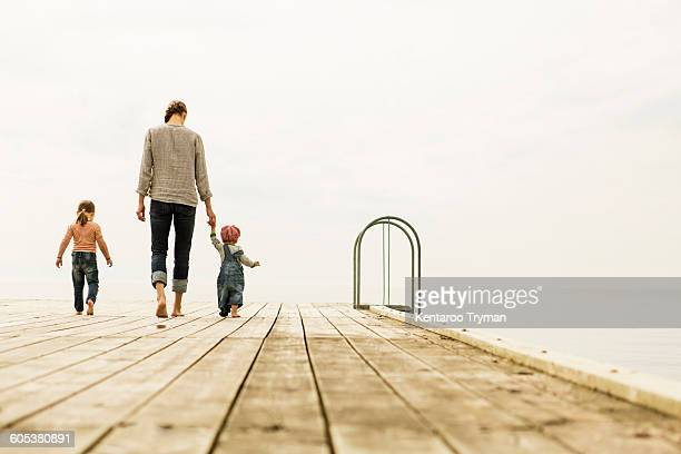 Full length rear view of family walking on pier at sea against clear sky