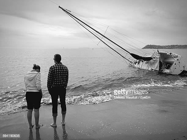 Full Length Rear View Of Friends Standing On Beach By Moored Sailboat