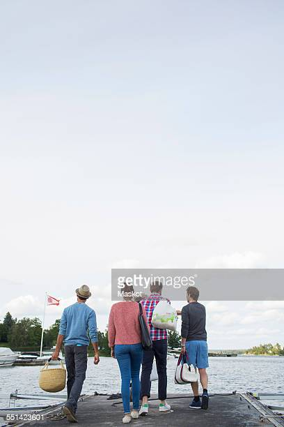 Full length rear view of friends walking on pier against sky