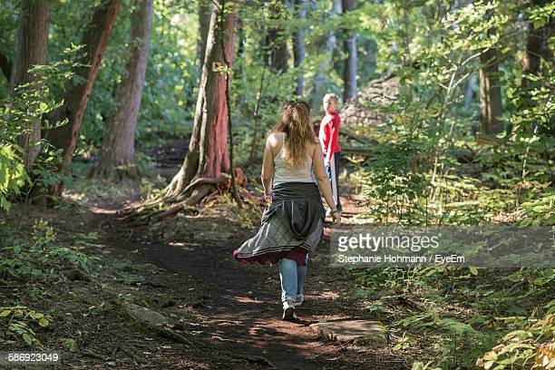 Full Length Rear View Of Girl Walking Towards Friend In Forest
