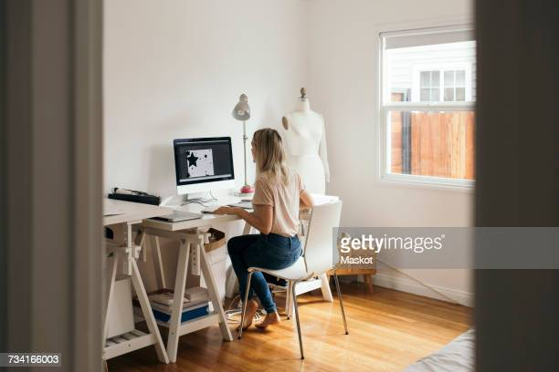 Full length rear view of graphic designer using computer at home