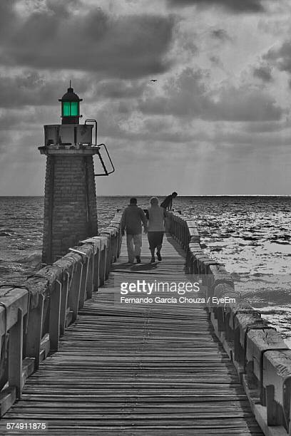 Full Length Rear View Of Man And Woman Walking On Pier