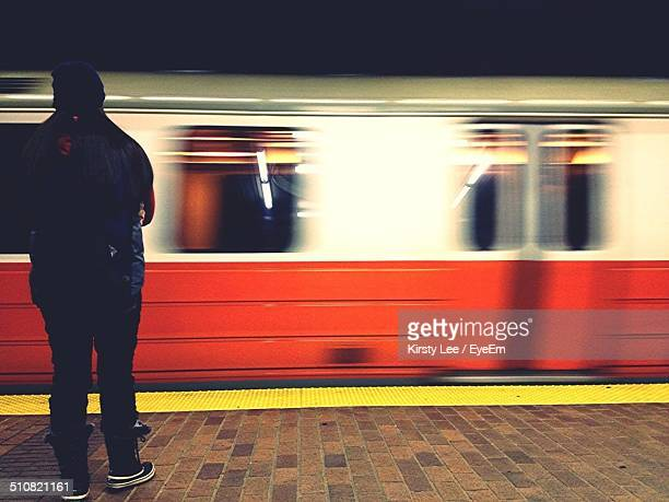 Full length rear view of man in front of train at station