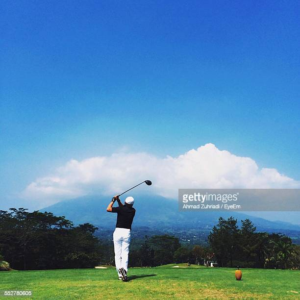 Full Length Rear View Of Man Playing Golf On Field