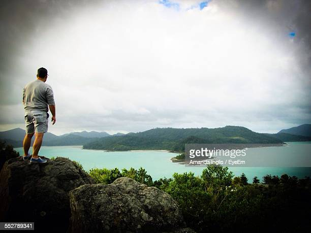 Full Length Rear View Of Man Standing On Rock By River And Mountains Against Cloudy Sky