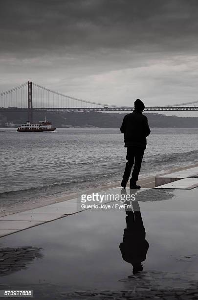 Full Length Rear View Of Man Walking By 25 De Abril Bridge Against Cloudy Sky At Dusk