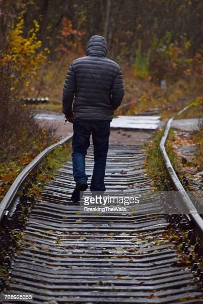 Full Length Rear View Of Man Walking On Train Tracks