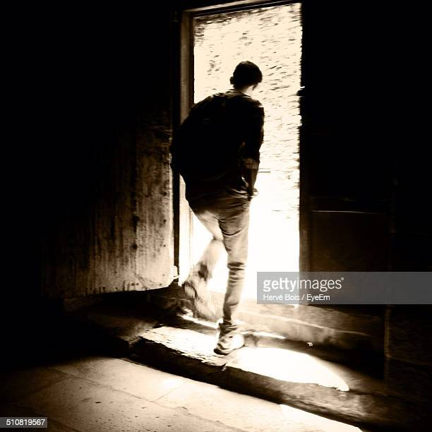Full length rear view of man walking out of house