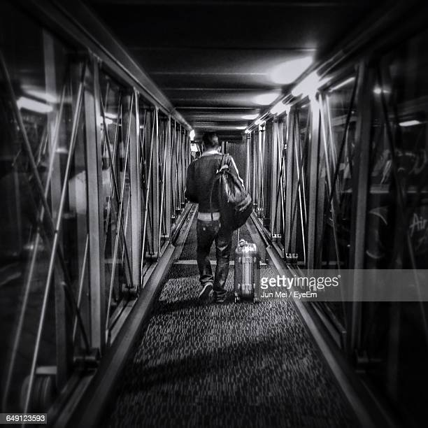 Full Length Rear View Of Man With Luggage Walking In Airport Corridor