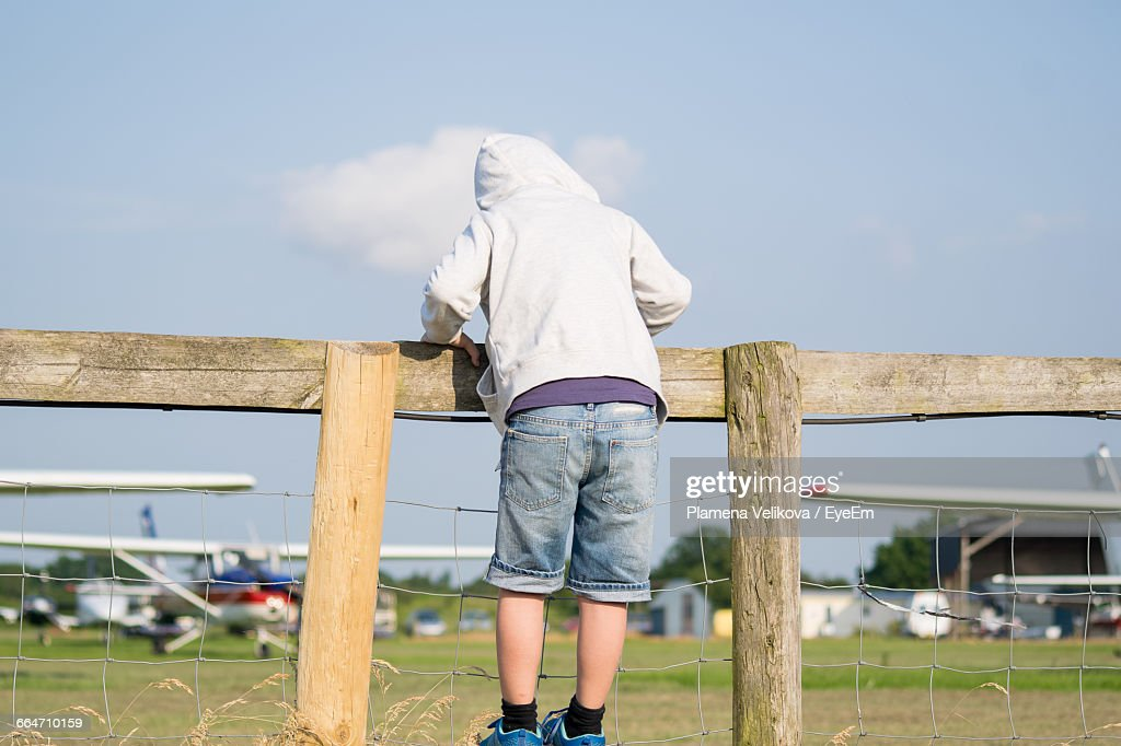 Full Length Rear View Of Person In Hooded Shirt Standing On Fence