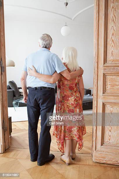 Full length rear view of senior couple standing with arms around at doorway in home