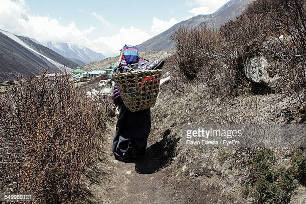 Full Length Rear View Of Woman Carrying Basket On Mountain Trail