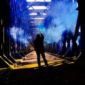 Full Length Rear View Of Woman Holding Distress Flare On Cantilever Bridge
