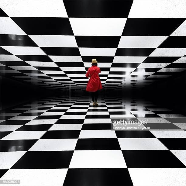 Full Length Rear View Of Woman Standing In Checked Pattern Passage
