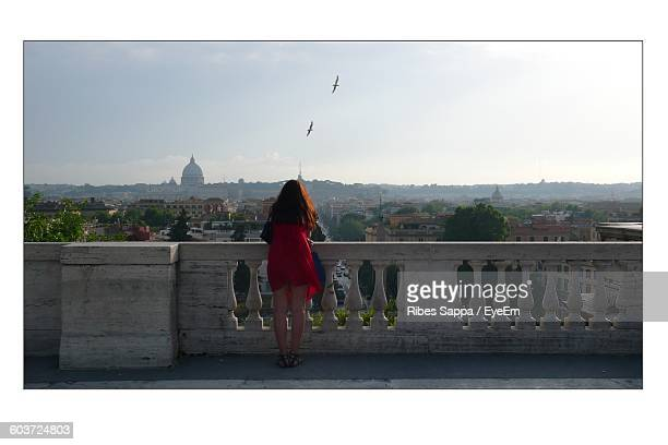 Full Length Rear View Of Woman Standing On Building Terrace In Town Against Sky