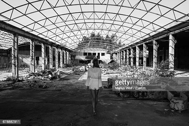 Full Length Rear View Of Woman Walking In Abandoned Warehouse