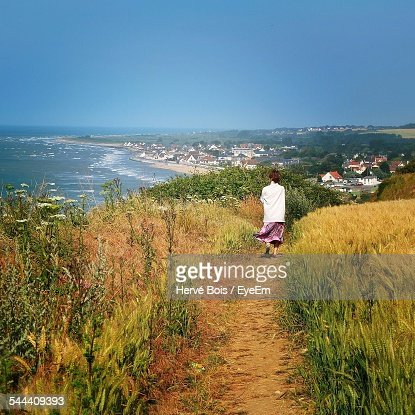 Full Length Rear View Of Woman Walking On Grassy Field By Sea Against Clear Blue Sky