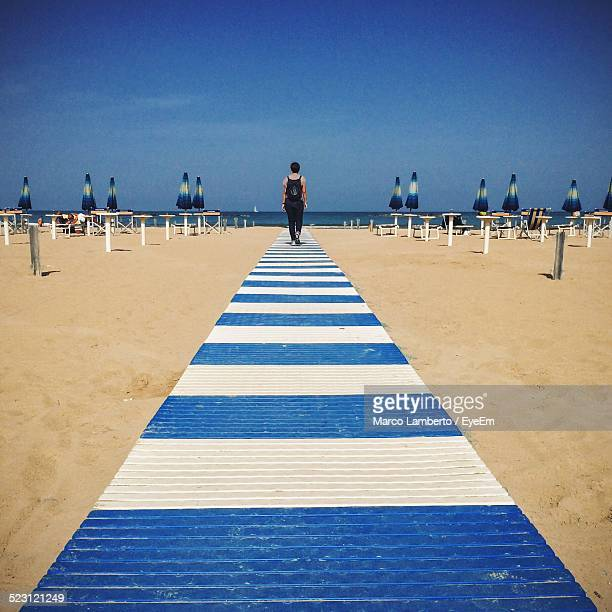 Full Length Rear View Of Woman Walking On Striped Pier At Beach
