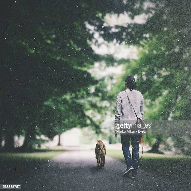 Full Length Rear View Of Woman Walking With Dog On Street