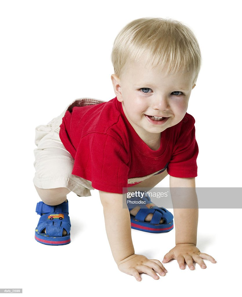full length shot of a blonde haired baby boy in a red shirt as he crawls : Stock Photo