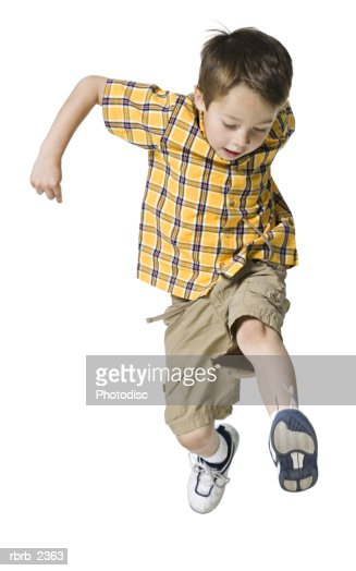 full length shot of a male child in a yellow shirt as he runs and jumps through the air : ストックフォト
