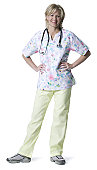 full length shot of an adult female nurse in colorful scrubs as she smiles at the camera