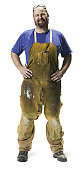 full length shot of an adult male in work overalls as he smiles at the camera