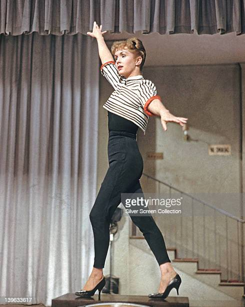 Full length shot of Debbie Reynolds US actress singer and dancer wearing black leggings and a black and white striped cropped tshirt holding a dance...