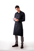Full length shot of young chef or waiter posing, wearing black apron and shirt, writing order on notepad, isolated on white background