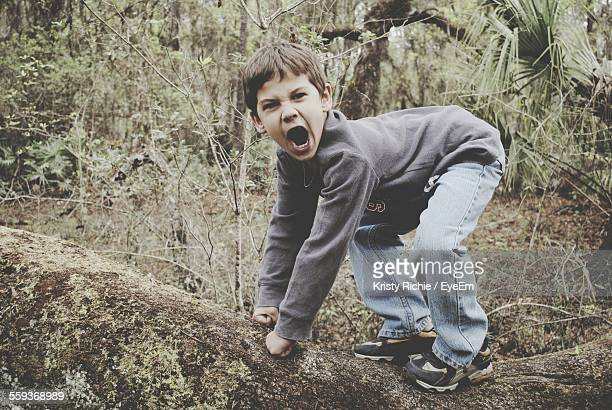 Full Length Side View Of Boy Imitating Gorilla In Forest