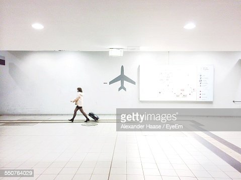 Full Length Side View Of Businesswoman With Luggage Walking In Airport Terminal