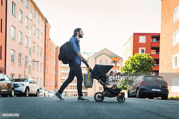 Full length side view of man pushing baby in carriage crossing city street