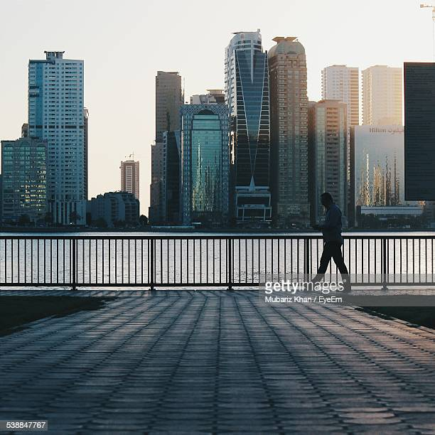 Full Length Side View Of Man Walking By Railing In City Against Sky