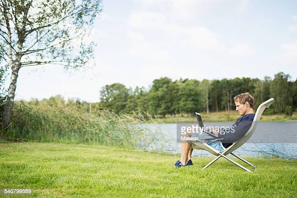 Full length side view of mature man using laptop on deck chair at lakeshore