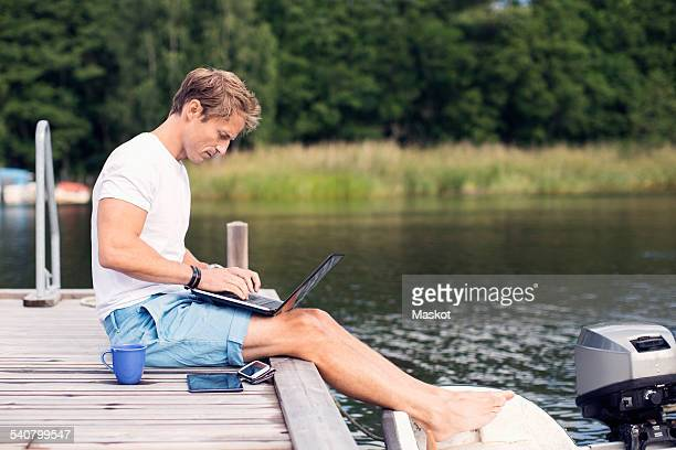 Full length side view of mature man using laptop on pier