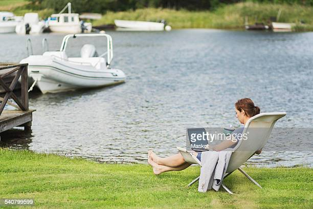 Full length side view of mature woman using laptop on deck chair at lakeshore