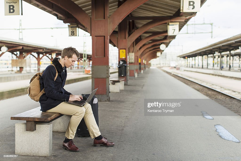 Full length side view of young businessman using laptop on railroad station