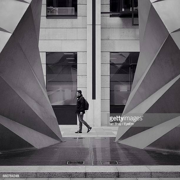Full Length Side View Of Young Man Walking On Footpath Against Building