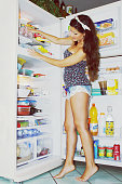 Full length side view of young woman searching food in refrigerator